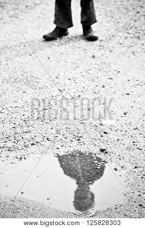 Reflection Of Obscured Face In Puddle