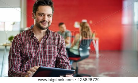 Casual portrait of a millenialbusiness man using technology in a bright and sunny startup with the team in the background