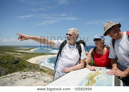 Senior group of hikers watching a plan
