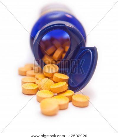 Bottle Of Orange Pills On White