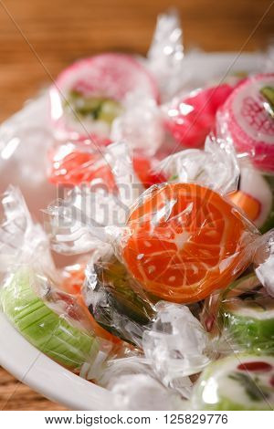 Few Fruit Candies With Fruit Motifs In White Bowl