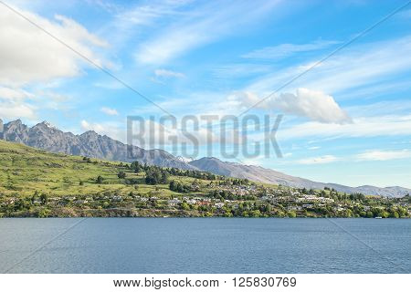 Beautiful blue sky with whie clouds overlooking Lake Wakatipu and Queenstwon New Zealand.