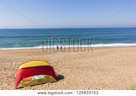 Beach tent blue ocean horizon with holiday bathers swimming coastline landscape.