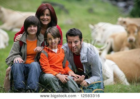 Portrait of a smiling family in the countryside in front of a herd of cows