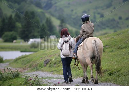 Woman walking near a little boy sitting on a pony