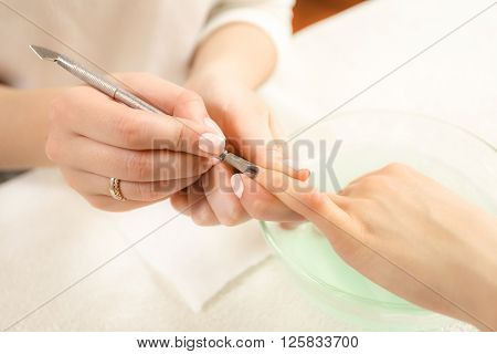 Close-up of Manicurist Removing Cuticle From The Nails of clients hand in spa salon. Beautician of cleaning female client nails