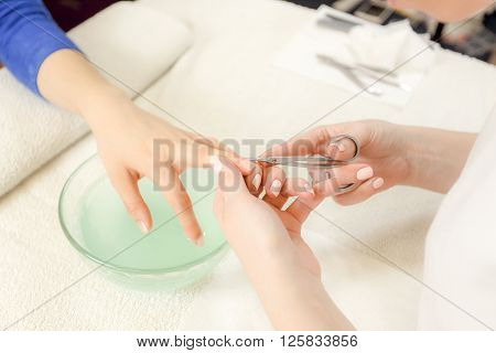 Closeup shot of a woman in a nail salon receiving a manicure by a beautician with nail scissors. Woman getting nail manicure. Beautician file nails to a customer.
