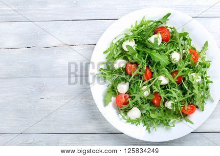 Dietary low calorie delicious salad with tomatoes mini mozzarella arugula on a white dish on a white rustic table studio light top view