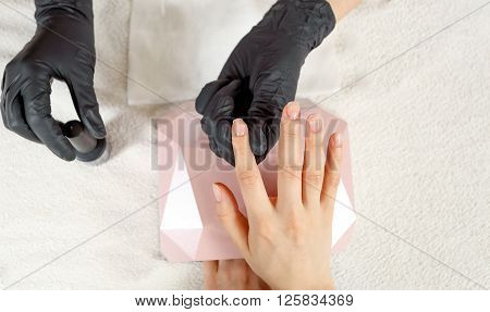 Top view manicurist holds customer hands. Fingernails are covered with clear nail polish