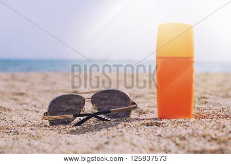Glasses and sun cream in the sand against the sea in the rays of sunlight and glare