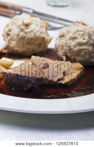 closeup of bavarian roasted pork with dumplings