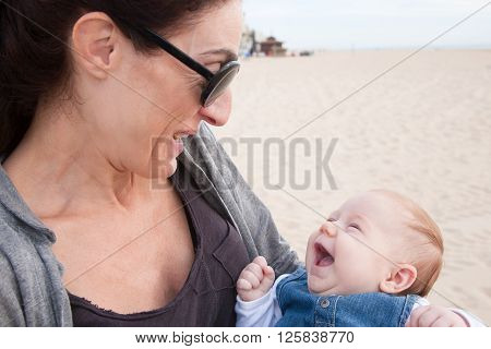 portrait of happy brunette woman mother grey shirt with two month age baby blue jeans dress embraced in her arms laughing in beach