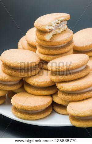 Sweet sandwich-biscuits filled with hazelnut cream arranged in a pyramid in a white plate with one bitten biscuit on top close up on dark neutral background.
