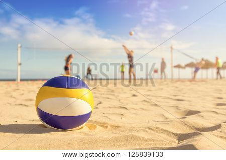 group of friends playing beach volleyball on sunny day