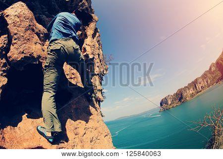free solo woman rock climber climbing at seaside