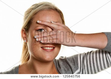 woman looks through fingers of her hand
