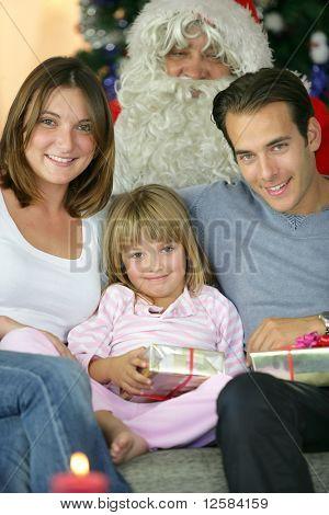 Retratos de un sonriente familia sentado en un sofá con Papá Noel