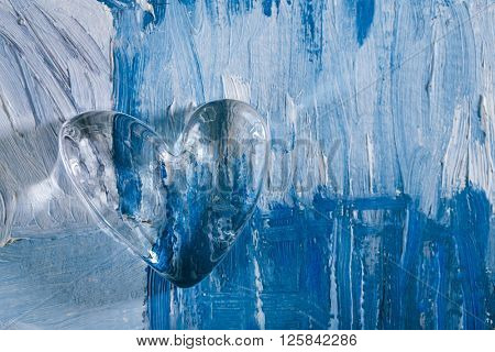 glass heart on blue abstract painted background