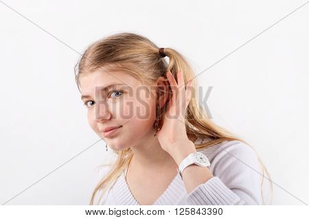 Young beautiful woman cant hear you so she cupping hand behind ear