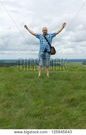 the man in a checkered shirt rejoices to conquest of the hill