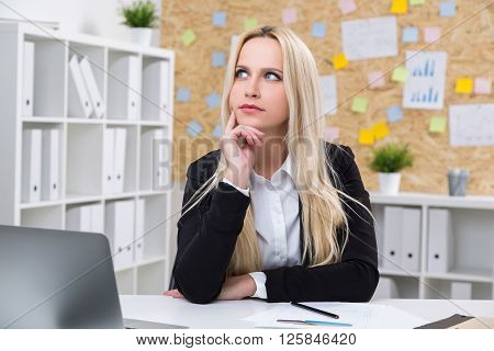 Thoughtful businesswoman at desk in office, close up