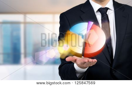 Businessman with colorful pie-chart on palm, close up