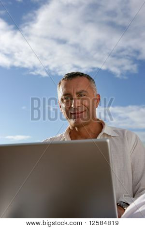 Portrait of a smiling man sitting in front of a laptop computer