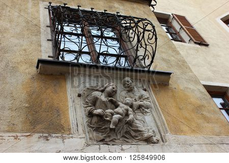Holy family bas-relief on the old house facade. The Holy Family depiction of Child Jesus, the Virgin Mary, Saint Joseph in plaster. Old bas-relief under window. Architectural detail on italian house.