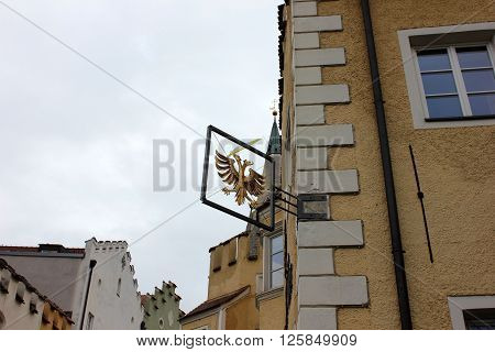 Two headed eagle coat of arms sign on the building. Gilded sign of the two headed bird attached to the old building. Ascending houses view. Architectural details of the old Italian house.