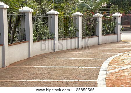 Patterned paved entrance lined by walled security fence