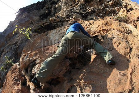 free solo woman rock climber climbing on mountain rock