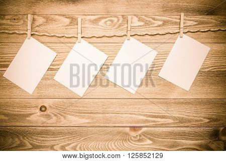 Blank paper sheets for text hanging on rope