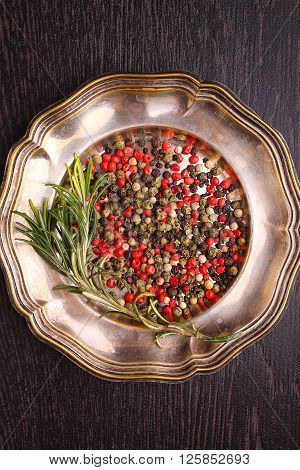a mixture of peppers ( red white black ) on the metal plate with a sprig of rosemary on a black background