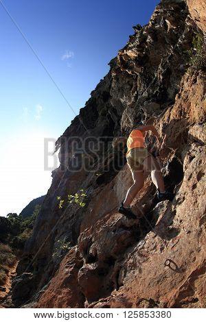 free solo woman rock climber climbing on mountain rock