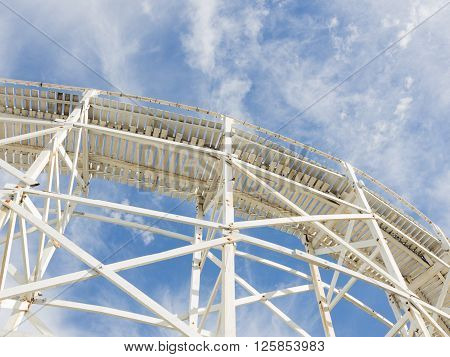 beautiful abstraction made of white wood of the old road on the background of blue sky with white cumulus and cirrus clouds