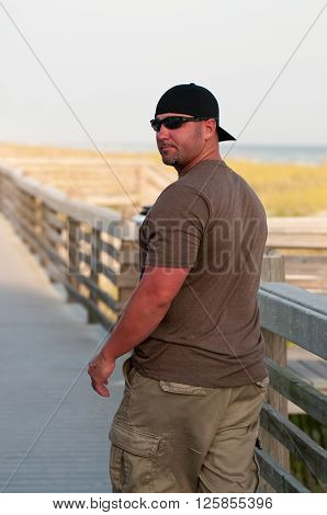 Handsome man in backwards ball cap looking back on a bridge.