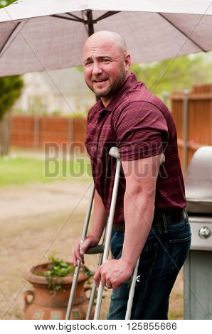 Muscular bald man on crutches standing outside. ** Note: Visible grain at 100%, best at smaller sizes