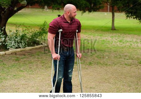Muscular and injured bald man on crutches standing outdoors.