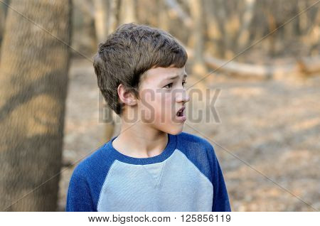 Outdoor photo of handsome young boy looking sideways outdoors.