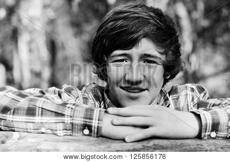 Close up of a cute teenage boy with long hair in black and white.