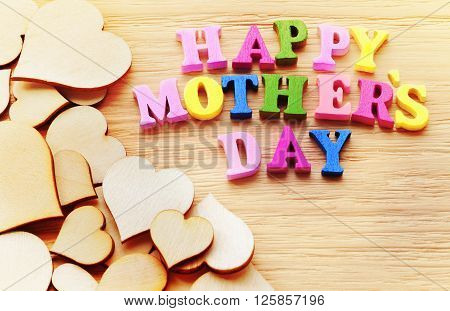 Happy Mothers Day colorful letters spelling greeting on rustic wood table with hearts