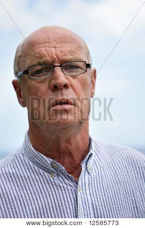 Portrait of a senior man skeptical with eyeglasses