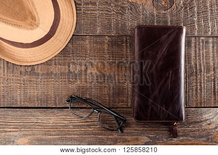 Top view photo of objects on wooden table. There are men's purse, hat and glasses