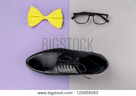 Top view photo of objects on two color table. There are men's shoe, yellow bow tie and glasses