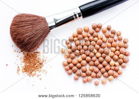 Cosmetics rouge balls with a brush isolated on white background
