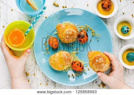 Easter treats for kids sweet buns bird traditional baking on spring holiday. Easter breakfast for the child beautiful composition with kid hands top view