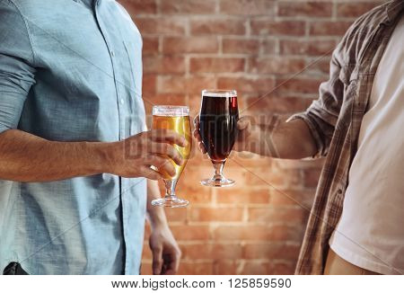 Two men clinking glasses of dark and light beer on brick wall background