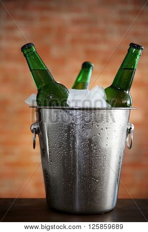 Green glass bottles of beer in ice-pail on brick wall background