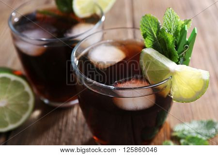 Two glasses of cola with ice, mint and lime on wooden table background