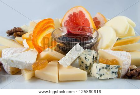 Salad with fruit, nuts, raisins, blue cheese, white cheese and jam.